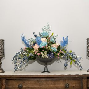 Blue Roses, Pink Cabbage Roses Arranged with Berry Pick and Curly Feathers in a Silver Glass Pedestal Urn