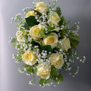 White Roses Baby Breath and Dusty Miller in an Oval White Ceramic Vase