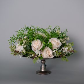 White Roses with Berries and Mahonia Grass in a Silver Pedestal Urn with an LED Candle