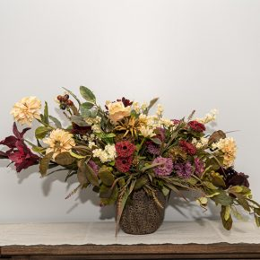 Burgundy Lilies, Red Berries, Assorted Mini Carnations Arranged in a Brown Cement Pot