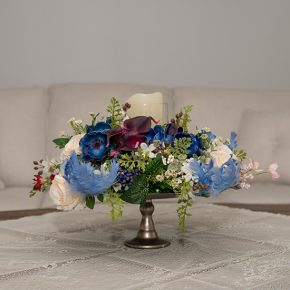 Dark Purple Cala Lily, Blue Anemone and Cream Cabbage Roses Decorated with Blue Curly Feathers and an LED Candle Arranged in a Silver Pedestal