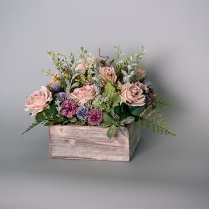Mauve Roses with Small Purple Carnations Decorated with Assorted Foliage in a White Wood Planter