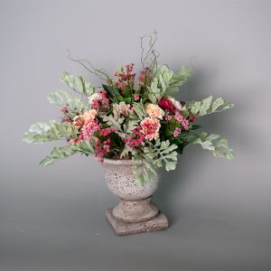 Mini Carnations with Dusty Miller and Pink Mahonia Grass in a Cement Urn