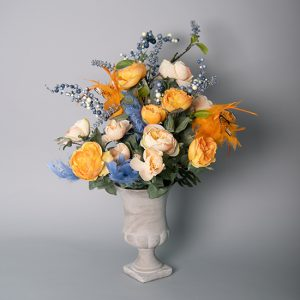 Orange and Peach Cabbage Rose with Blueberry Astilbe Spray decorated with Feather in a Grey Cement Urn